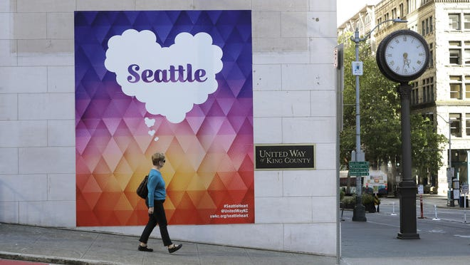 In this Tuesday, June 16, 2020, photo, a pedestrian walks past the headquarters for United Way of King County, in downtown Seattle. A recession is expected to curtail Americans' generosity following a record year for charitable donations. But the recent wave of money dedicated to fighting the coronavirus and racial inequality in the U.S. is offering a beacon of hope for nonprofits in 2020. United Way, a nonprofit that relies heavily on middle-class donors, said it has raised $900 million worldwide since mid-March.
