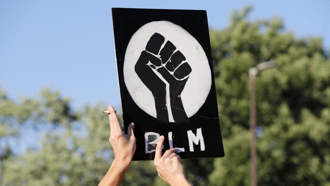 A protester holds up a Black Lives Matter sign outside the police station Wednesday, June 10, 2020, in Florissant, Mo. Demonstrators were calling attention to a video that appears to show a Florissant police detective, who has since been fired, striking a man with his police car during a recent pursuit.
