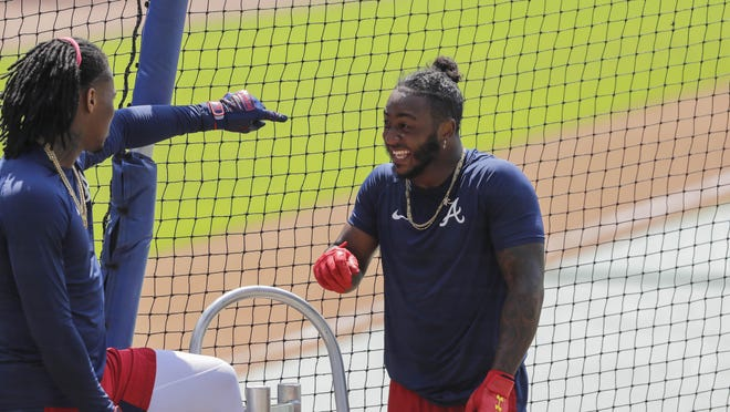 The Atlanta Braves' Ozzie Albies, right, laughs with Ronald Acuña Jr. before batting during team baseball practice at Truist Park on Sunday in Atlanta.