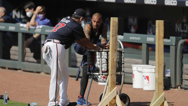 Atlanta's Nick Markakis (right) talks with a coach during team practice at Truist Park on Sunday.
