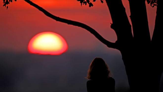 A woman watches the sunset from a park Friday, July 3, 2020 in Kansas City, Mo.