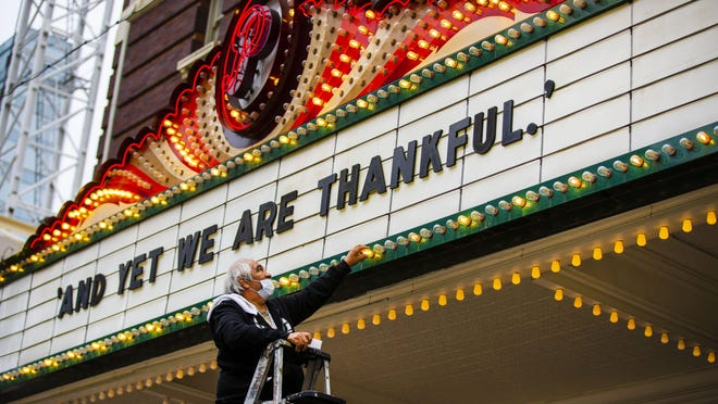 """Robert Luna installs light bulbs and the wording""""And Yet We Are Thankful """" on The marquee on the Paramount Theater on Congress Avenue in Austin on Monday, November 23, 2020."""