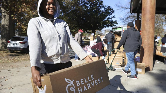 Crystal Cobb picks up a box of food Monday in Memphis, Tenn. Tracy and Keith Millbrook started their own nonprofit, We Are Family, which despite the pandemic gave away food for the 10th straight year this Thanksgiving.