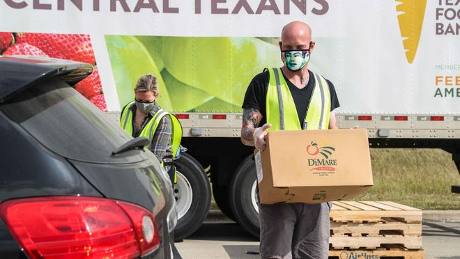 Volunteer Patrick Voellmar helps Central Texas Food Bank distribute food boxes at Turner Robert Recreation Center in Austin on Oct. 15.