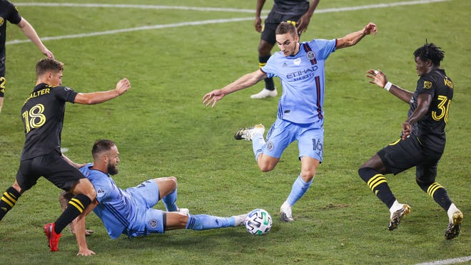 New York City FC midfielder James Sands takes a shot in front of fallen teammate Alexander Callens as Crew defender Aboubacar Keita, right, and midfielder Sebastian Berhalter defend during the second half on Monday night in Harrison, N.J. NYCFC scored in the 59th minute and won 1-0.