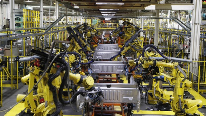 In this Sept. 27, 2018 file photo, robots weld the bed of a 2018 Ford F-150 truck on the assembly line at the Ford Rouge assembly plant in Dearborn, Mich. The U.S. auto industry's coronavirus comeback plan was pretty simple: restart factories gradually and push out trucks and other vehicles for waiting buyers in states left largely untouched by the virus outbreak.Yet the return from a two-month production shutdown hasn't gone quite according to plan.