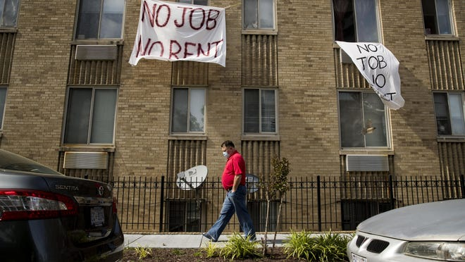 """In this May 20, 2020 file photo, signs that read """"No Job No Rent"""" hang from the windows of an apartment building in Northwest Washington. Renters are nearing the end of their financial rope as the assistance and protections given to them during the pandemic run their course."""