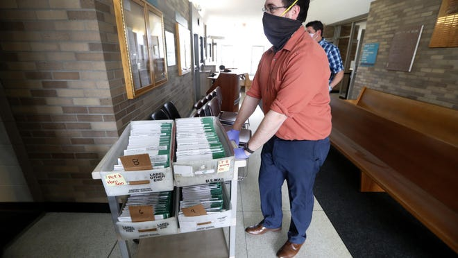 Jordan Smellie moves absentee ballots to be counted at city hall in Garden City  Tuesday, May 5, 2020. People in about 50 Michigan communities are participating in largely mail-based local elections that might be a blueprint for the presidential battleground state in November.