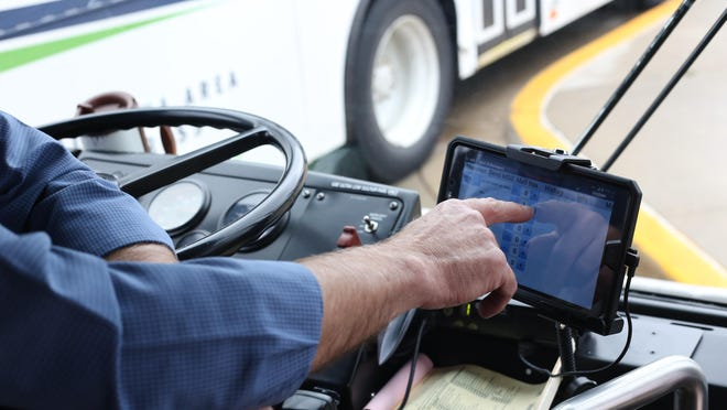 A bus driver uses a tablet on a Macatawa Area Express bus. The MAX bus system is moving to an electronic payment system on Oct. 1.