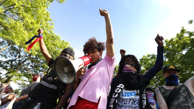 Stefan Perez raises his fist while addressing a rally in Detroit, Wednesday, June 3, over the death of George Floyd, a black man who was in police custody in Minneapolis. Floyd died after being restrained by Minneapolis police officers on Memorial Day.