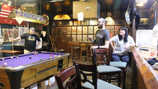 Matt Helms, left, chats with Zach Preston and his wife Allie Preston at The Leon Pub in Tallahassee, Fla., on Monday night, Sept. 14, 2020. They have been regulars at the once-popular watering hole, which is trying to revive its business in the wake of the coronavirus pandemic.