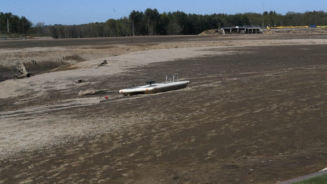 FILE- In this May 21, 2020, file photo, Wixom Lake is drained of water after the Edenville Dam failed and flood waters rushed south, ravaging the landscape in its path, in Edenville Township, Mich. With more snow inevitably on its way this winter, county officials are warning residents about the dangers that the now-dry lakebeds pose, especially to those who partake in winter recreations such as snowmobiling.