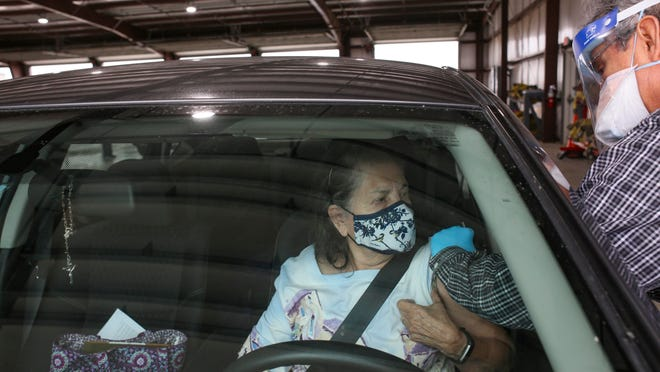 Gloria Garcia waits in her car while physician assistant Paul Toscano administers her dose of the Moderna COVID-19 vaccine Thursday at Cameron County's COVID-19 vaccine clinic at the Los Fresnos Fire Station & EMS in Los Fresnos, Texas.