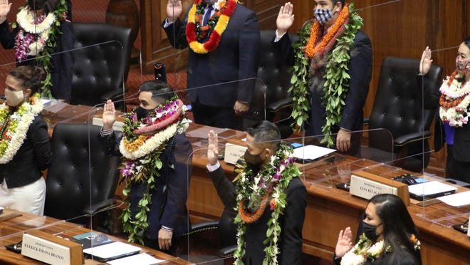 Members of the Hawaii House are sworn in Honolulu on Wednesday. Lawmakers opened a new legislative session in the middle of a pandemic while wearing face masks and sitting next to clear plastic shields separating their seats.