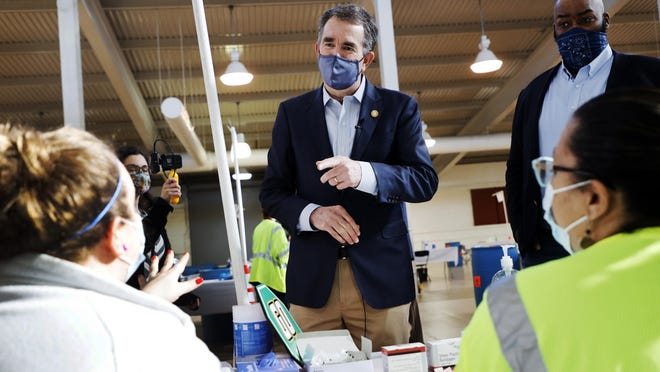Virginia Gov. Ralph Northam talks with two volunteers who were administering COVID-19 vaccinations at the Richmond Raceway complex in Richmond, Va., on Thursday. At right is Del. Lamont Bagby, D-Henrico.