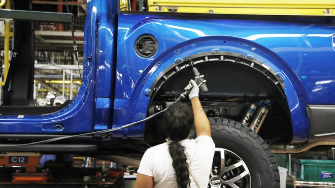 FILE- In this Sept. 27, 2018, file photo a United Auto Workers assemblyman works on a 2018 Ford F-150 truck being assembled at the Ford Rouge assembly plant in Dearborn, Mich. Ford Motor Co. said Thursday, Feb. 4, 2021, that it will cut shifts at two of its U.S. manufacturing plants next week, due to the worldwide chip shortage that has also impacted other automakers. Ford will cut shifts at its Dearborn, Mich., facility and  Kansas City, Mo., plant; both produce the F-150 pickup truck, Ford's most popular model and part of the F-Series, the top-selling vehicle in the U.S.