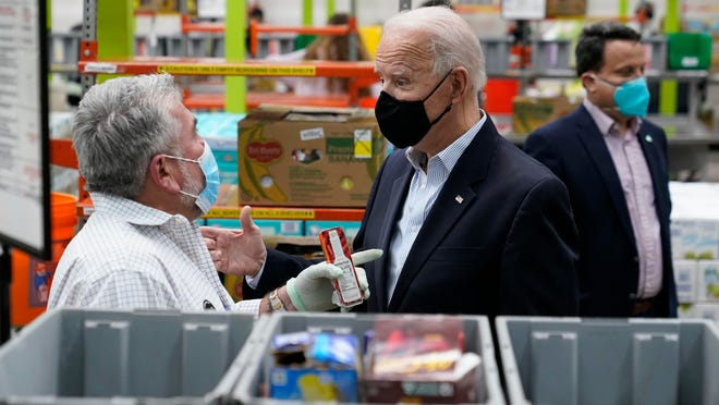 President Joe Biden talks with a volunteer at the Houston Food Bank on Friday.