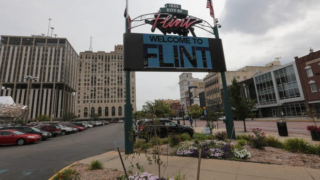 A video sign flashes a Welcome to Flint sign off of Saginaw Street in downtown Flint in 2013.