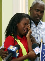 Ronyde Ponthieux, 10, cries as her father Rony hugs