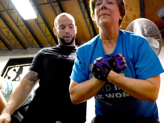 Seaford Powerhouse Gym 24/7 head trainer Scott Ousley critiquing workout by 57-year-old Becky Evaristo, a take it off participant.