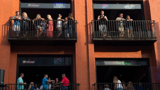Pedestrians occupy the balconies of Honky Tonk Central along Broadway during the 2018 CMA Music Festival on Thursday, June 7, 2018, in Nashville, Tenn.