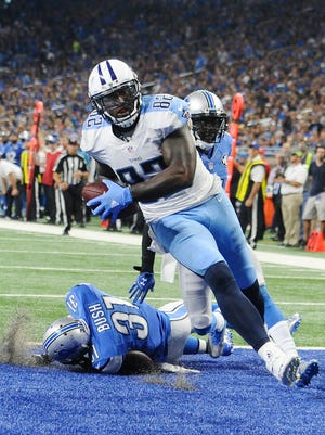 Titans' Delanie Walker rumbles into the end zone with Lions Rafael Bush and Nevin Lawson for a touchdown in the fourth quarter.