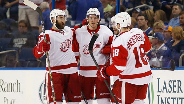 From left, Kyle Quincey and Danny DeKeyser gather with teammates after Detroit's first goal, by Riley Sheahan, on Saturday.