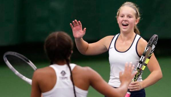 Bay Port's Rachel Ceaglske (right) high-fives teammate Devan Perry in a Division 1 doubles match at the WIAA state tennis tournament at the Nielsen Tennis Stadium in Madison.