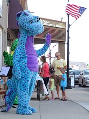 A large dinosaur greets children with a friendly wave