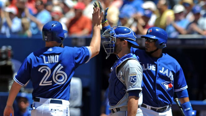 Adam Lind is greeted at home plate after scoring by designated hitter Edwin Encarnacion.