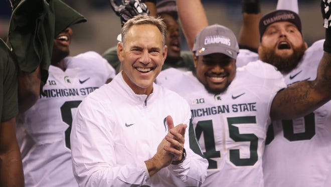 Michigan State coach Mark Dantonio celebrates after the 16-13 win against the Iowa Hawkeyes in the Big Ten championship Dec. 5 at Lucas Oil Stadium in Indianapolis.