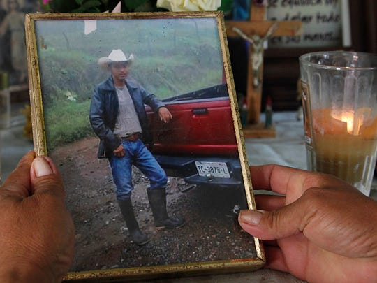 In this July 15, 2016 photo, Maria Felix Martinez Chavez holds a photo of her late son, Jose Rangel Chavez, placed next to a lit candle on an altar in his honor in El Sabino, Mexico. Chavez went to the U.S. with legal permission as part of a guest worker program, with the goal to pay for his parents to build a more solid home, and dutifully wired money back whenever he could. The 22-year-old and five other workers were killed on Nov. 6 on a highway as they were returning to Mexico in a bus provided by their employer.