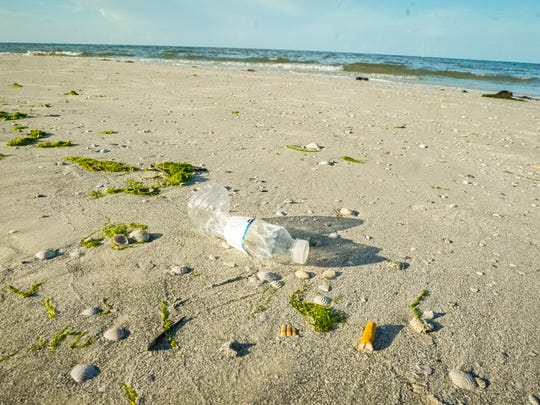 A plastic water bottle and a cigaret bud litter Fort Myers Beach on June 17, 2017.  The town of Fort Myers Beach is considering banning the retail sale of plastic drinking straws within its boundaries. This would include a prohibition for use by town restaurants. Plastic drinking straws don't degrade quickly, and are considered an environmental threat. The Lani Kai hotel already has switched to wax-coated paper straws. It is not always easy to find straw litter on the beach but the bright green color makes them easy to sport for quick pick up even in the dark.