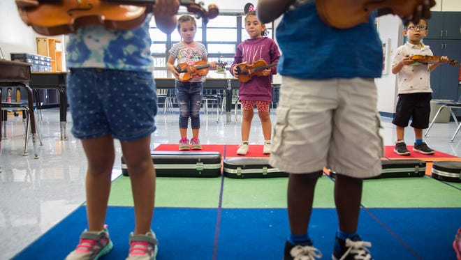 Adalynn Falzon, 5, left, Camille Rivero, 4, center, and Isaac Menjivar, 5, right, learn where to hold their violins before they play during the MusicScores! program at Avalon Elementary School on Wednesday, Jan. 24, 2018.