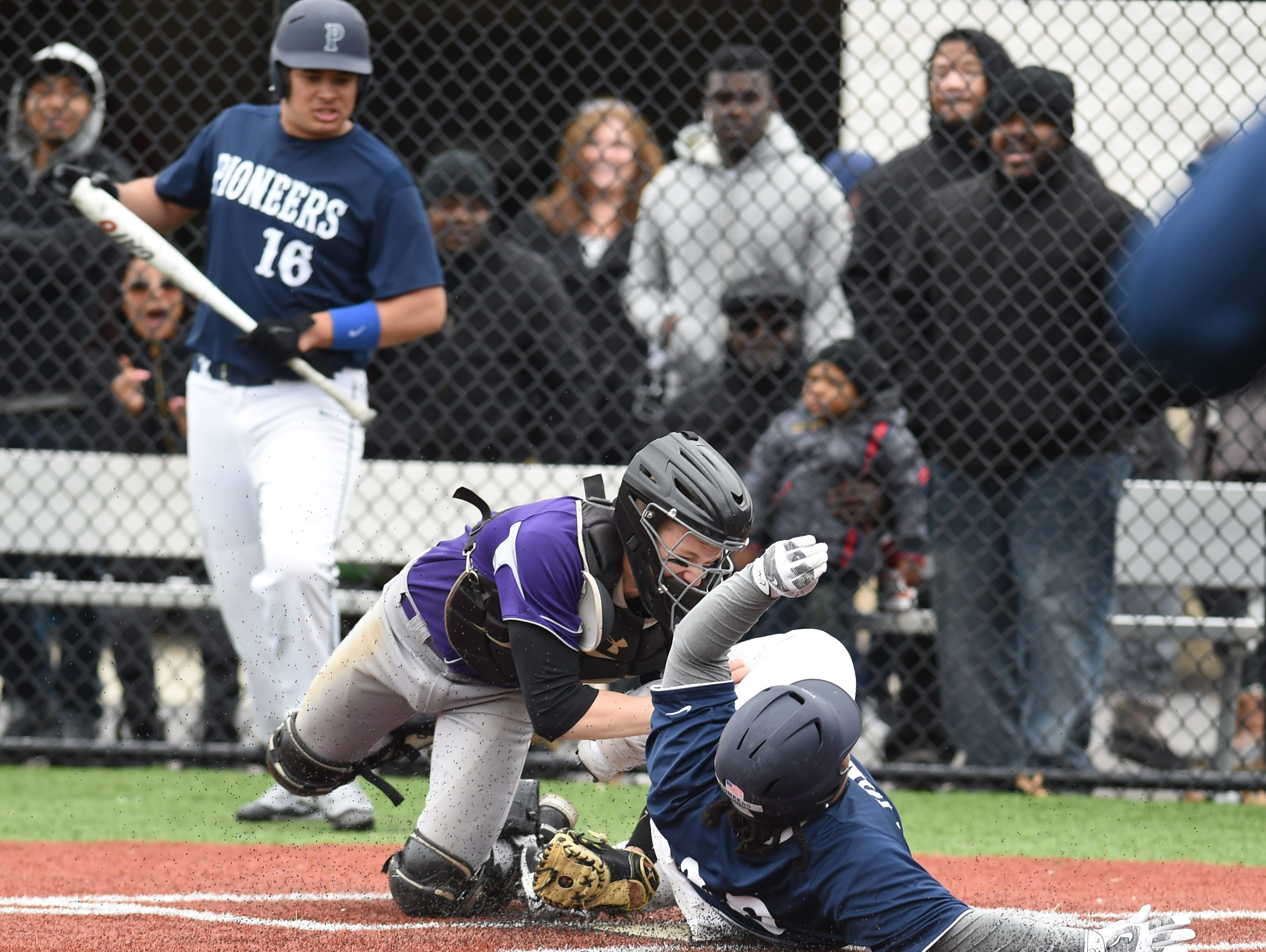 Poughkeepsie's Marcus Blocker slides into home under Rhinebeck's Spencer Hutchins during Saturday's game at Poughkeepsie High School.