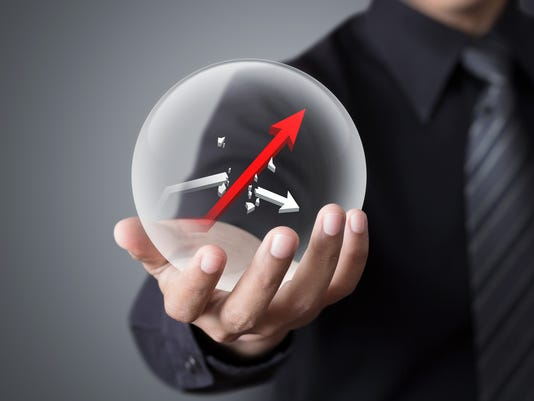 Businessman holds crystal ball with rising red graph