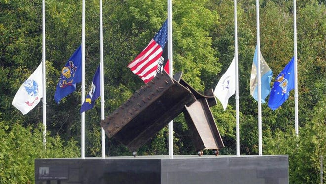 In this Sept. 11, 2013 file photo, flags fly at half-mast behind a piece of wreckage from the World Trade Center that is displayed at Franklin County Veterans and 9/11 Memorial Park at Letterkenny Chapel.