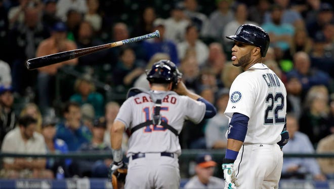 Seattle Mariners' Robinson Cano (22) tosses away his bat after striking out as Houston Astros catcher Jason Castro heads to his dugout in the sixth inning of a baseball game Monday, April 20, 2015, in Seattle.
