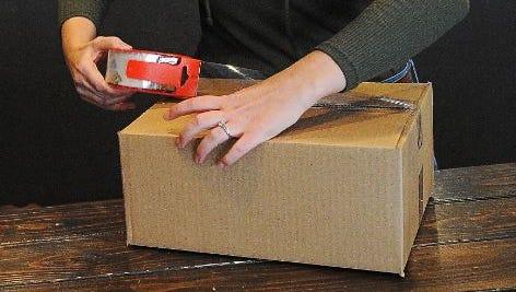 A retailer prepares an online order for shipping.