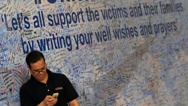A man checks his mobile phone in front of a message board for passengers aboard a missing Malaysia Airlines plane at a shopping mall in Petaling Jaya, near Kuala Lumpur.