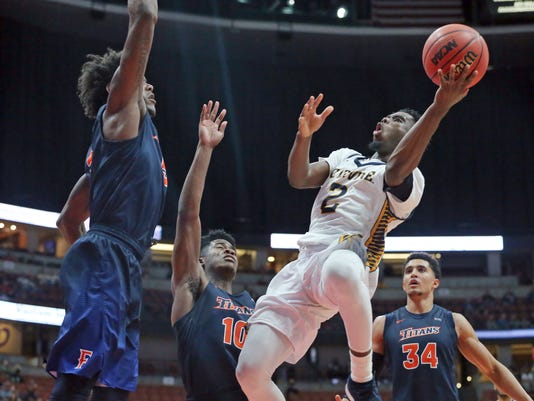UC Irvine guard Max Hazzard (2) shoots as Cal State Fullerton forward Davon Clare, left, defends during the first half of an NCAA college basketball game for the Big West men's tournament championship in Anaheim, Calif., Saturday, March 10, 2018. (AP Photo/Reed Saxon)