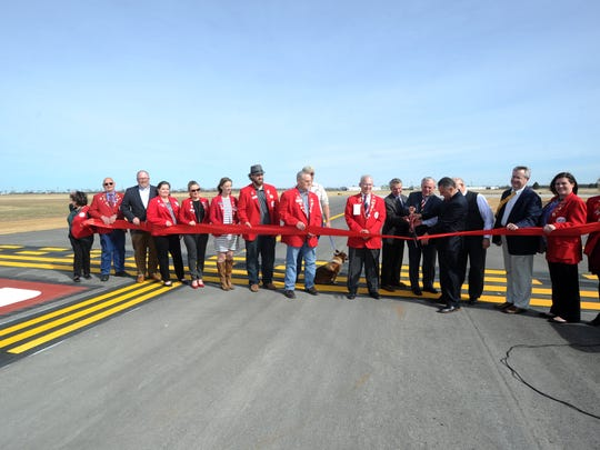 The Abilene Chamber of Commerce Redcoats take part in a ribbon-cutting to celebrate the completion of a new runway at Abilene Regional Airport.