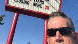 Restaurant owner Mike Douglas stands in front of a sign announcing the planned closing date.