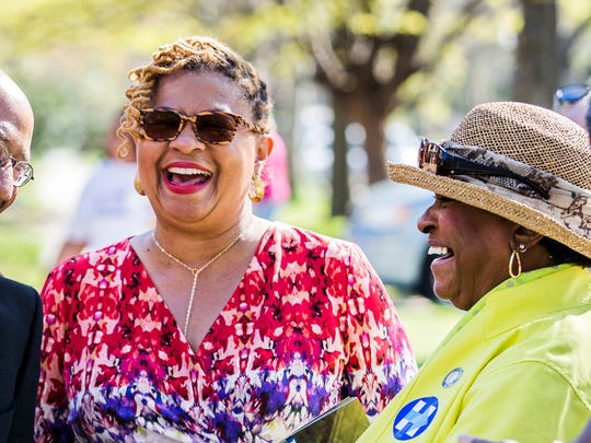 Tony Lawrence hugs former Philadelphia Mayor Michael Nutter as they share a laugh with Rep. Stephanie Bolden (right) and Councilwoman Hanifa Shabazz outside Lawrence's home in Wilmington on Sunday afternoon. Nutter, Bolden and Shabazz spent the afternoon canvassing with other local politicians for Hillary Clinton.
