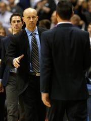 Xavier head coach Chris Mack (left) shakes hands with