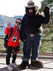 A Bahraini athlete poses for a photograph with Smokey the Bear. Twenty-two Bahraini athletes spent the afternoon at Mount San Jacinto on Wednesday.