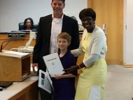 Mayor Ollie Tyler presents Joey Gouthiere with a proclamation