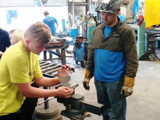 Fort Braden student and Carl Wolaver shaping a butterfly.