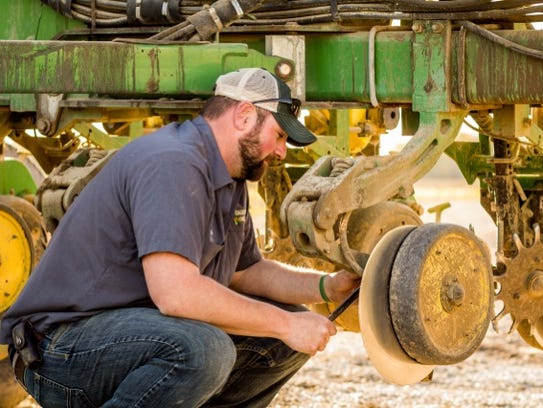 Scott Thomas works on a farm implement. The Brown City
