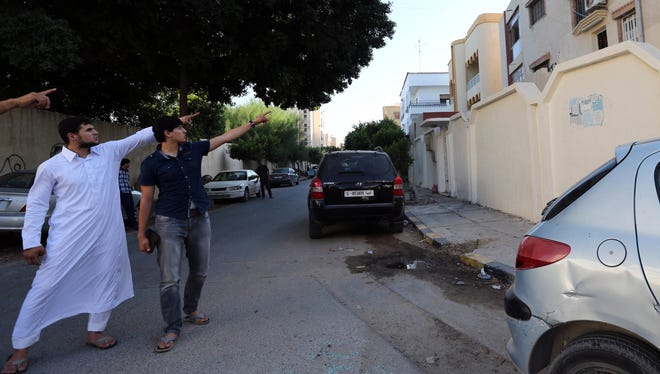 """Abdullah al-Raghie (L) and Abdul Moheman al-Raghie (C), the sons of al-Qaeda suspect Abu Anas al-Libi point at the house next to the scene where their father was kidnapped by US special forces in a commando raid in Nofliene, five kilometres from the Libyan capital Tripoli on October 6, 2013, sealing a 15-year manhunt for him. Libya said it had demanded an explanation from Washington for the """"kidnap"""" of a citizen in an unauthorised commando raid on its territory that netted a top Al-Qaeda suspect.  AFP PHOTO / STRSTR/AFP/Getty Images ORIG FILE ID: 523564991"""